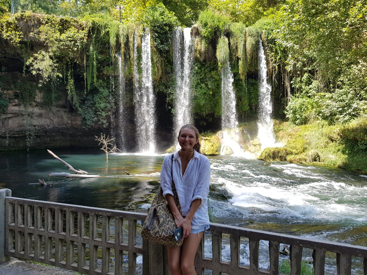 Female in front of luscious green waterfall